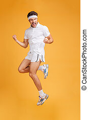 Happy handsome young sportsman shouting and jumping in the...