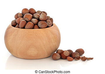 Hazelnuts in a beech wood bowl and scattered, isolated over...
