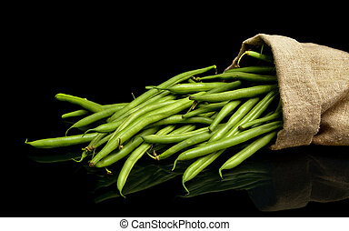Stack of green beans in linen sack on black background