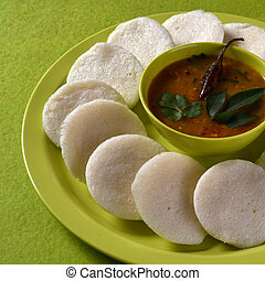 Idli with Sambar in bowl on green background, Indian Dish :...