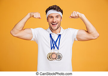 Cheerful young spotrsman with three medals showing biceps