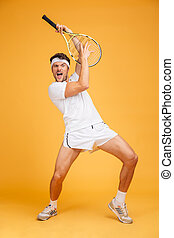Comical playful young man tennis player with racket having...