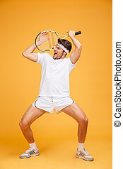 Amusing young man tennis player holding racket and having...
