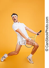 Man tennis player with racket singing and imitating playing...