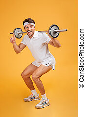 Fitness man doing exercises with barbell and showing thumbs...
