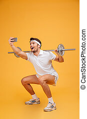 Happy man athlete working out with barbell and making selfie...