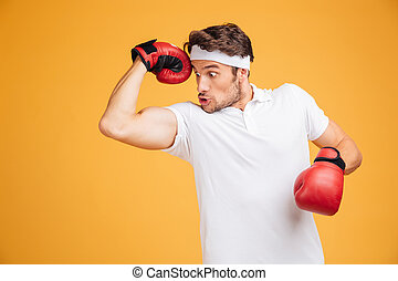 Amazed comical man boxer in red gloves showing his biceps -...