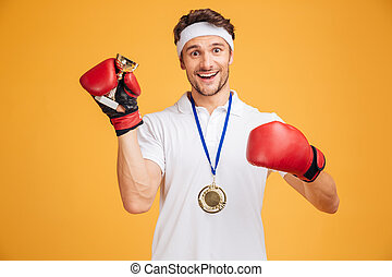 Man boxer in red gloves and medal holding trophy cup