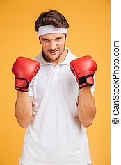 Portrait of strong young man boxer in red gloves over yellow...