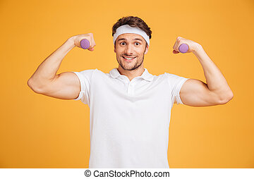 Cheerful young sportsman holding dumbbells and showing biceps