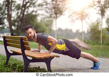 Young man working out doing push-ups on a wooden park bench...