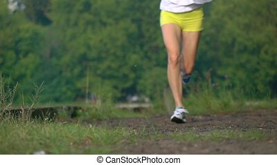 Super slow motion telephoto video of athletic woman running...