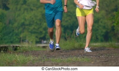 Super slow motion telephoto video of athletic girl and man running together towards the camera, 240 fps