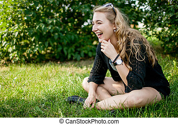 girl in black on the grass in the park in a good mood