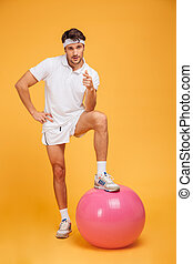 Young handsome sportsman with fitness ball pointing at camera