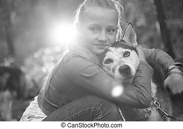 black and white photo of a girl hugging her dog husky on the background leaves in spring