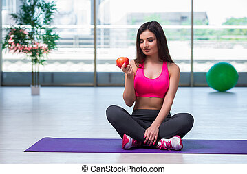 Young woman eating red apple in health concept
