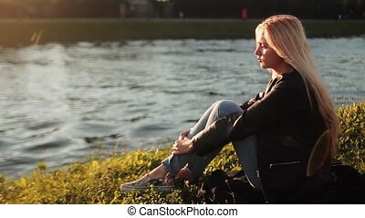 Young girl resting on the green grass near the river at sunset