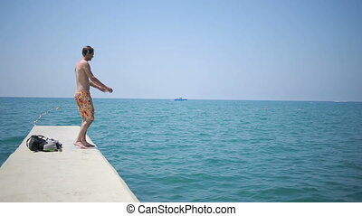 Man plunging in the water. tourist swims in the sea. Blue water and waves