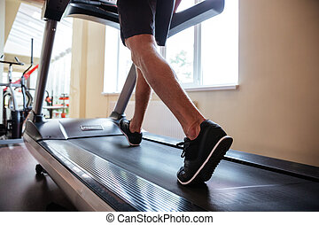 Legs of young fitness man running on treadmill in gym -...