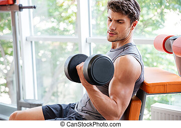 Sportsman doing exercises for biceps using dumbbells in jym...