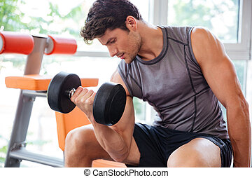 Fitness man working out with dumbbells in gym - Concentrated...