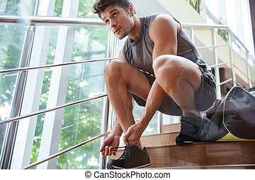 Man athlete sitting and tying laces on stairs - Handsome...