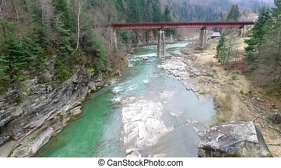 beautiful landscape with river and bridge in Carpathians -...