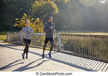 happy couple running outdoors - fitness, sport, people and...