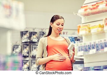 happy pregnant woman with medication at pharmacy