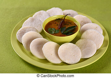 Idli with Sambar in bowl on green background, Indian Dish :...