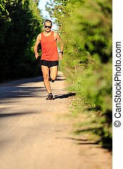 Man running on country road and training - Man runner...