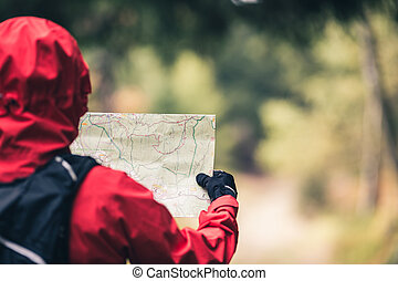 Woman hiking with map in autumn woods