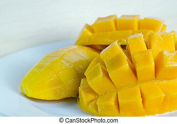 Mango nicely cut on wooden background (Also known as horse mango, Mangifera foetida, Anacardiaceae, Mangifera, M. indica)