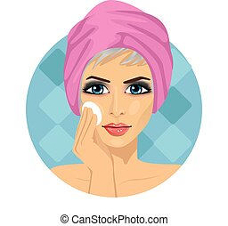 beautiful woman with towel around her head cleaning her face with sponge