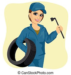beautiful working woman in car repair service holding tyre and wheel wrench
