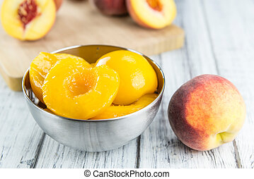Portion of preserved Peaches (close-up shot) on wooden...