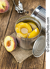 Canned Peaches (close-up shot) on vintage wooden background