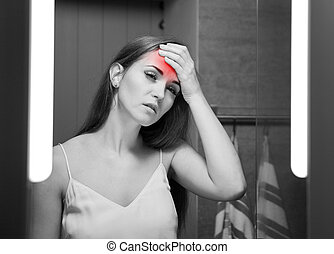 Woman with headache in front of a bathroom mirror