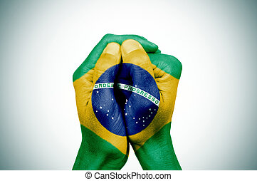 hands patterned with the flag of Brazil - closeup of the...
