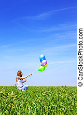 Girl in a field with balloons