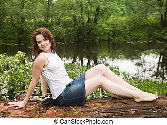 girl in wet shirt on old tree during rain