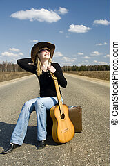country girl with guitar sits on road solitary under sky
