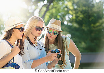 Friends looking at photos on their camera at summer vacation