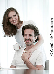 Portrait of happy couple embracing on white background