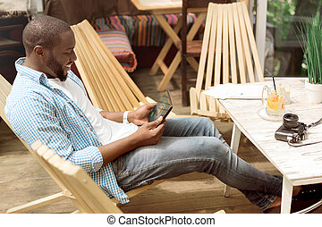 Pleasant smiling man using tablet - Share your emotions....