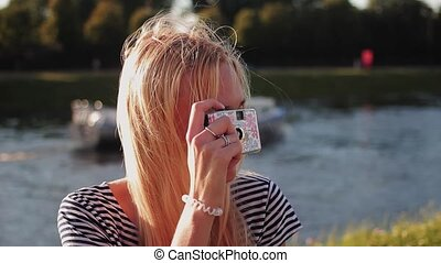 Young woman with a film camera taking pictures and laughs