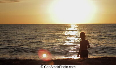 Little boy stay in calm sea at sunset. Silhouette