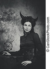 Black and white retro photo, woman demon, devil. Girl with...