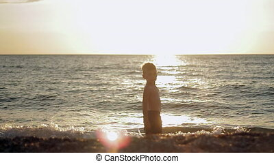 Little boy stay in calm sea at sunset. Slowmotion